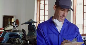 Male mechanic writing on clipboard in motorbike repair garage 4k. Front view of Caucasian male mechanic writing on clipboard in motorbike repair garage. He is stock video footage