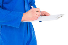 Male mechanic writing on clipboard. Over white background Stock Photo