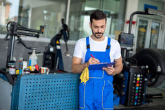 Male mechanic writing on clipboard. In repair shop Stock Images
