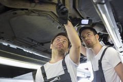 Male mechanics examining car in workshop Stock Photography