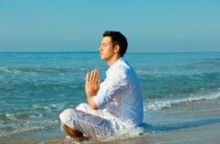 Male mediation beach. Guy meditating on the sea with upcoming waves Stock Images