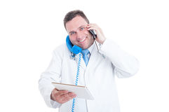 Male medic being busy and multitasking with phone and tablet Stock Photo
