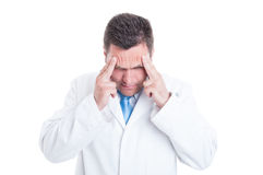 Male medic or doctor suffering a headache or stress. Male medic or doctor suffering a headache or being stressed isolated on white background with copy space Royalty Free Stock Image