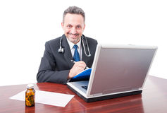 Male medic at office smiling and writing on clipboard. Isolated on white background Stock Photos