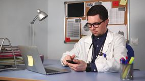 Male medic in white coat with stethoscope sitting at desk and using smart watch.