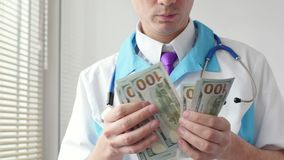 Male medical doctor counting hundred dollars banknotes. Close-up. Medic personnel salary, prestige and high paid job. Variant of corruption through medical stock video footage