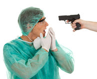Male medical doctor and gun Royalty Free Stock Image