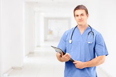 A male medical doctor in a uniform holding a clipboard and posin Royalty Free Stock Photo