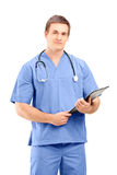 A male medical doctor in a uniform posing with clipboard in his Stock Image