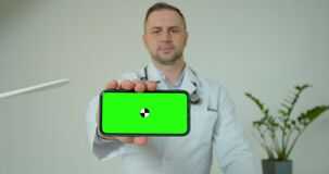 Male medical professional displaying mobile smartphone with greenscreen. Doctor man holding phone with green screen up