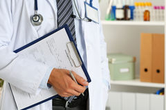 Male medicine doctor hand holding silver pen and clipboard. Pad closeup. Ward round, patient visit check, medical calculation and statistics concept. Physician Royalty Free Stock Photography