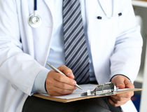 Male medicine doctor hand holding silver pen writing. Something on clipboard closeup. Ward round, patient visit check, medical calculation and statistics Royalty Free Stock Images