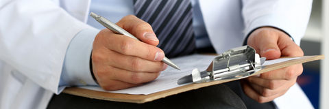 Male medicine doctor hand holding silver pen writing Stock Photos