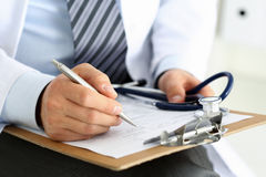 Male medicine doctor hand holding silver pen writing Stock Images