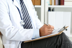 Male medicine doctor hand holding silver pen writing. Something on clipboard closeup. Ward round, patient visit check, medical calculation and statistics Royalty Free Stock Photo