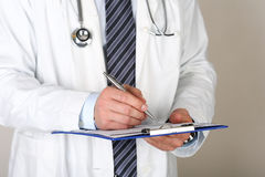 Male medicine doctor hand holding silver pen writing something o. N clipboard closeup. Medical care, insurance, prescription, paper work or career concept Royalty Free Stock Images