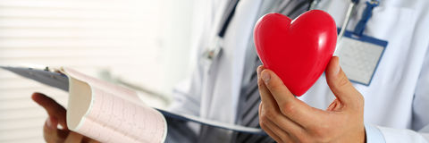 Male medicine doctor hands hold red toy heart and cardiogram chart. On clipboard pad. Cardio therapeutist, physician make cardiac physical, pulse rate measure stock photos