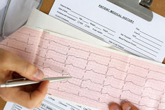 Male medicine doctor hands hold and show to patient cardiogram Stock Image