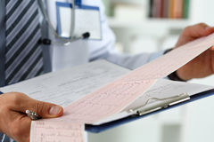 Male medicine doctor hands holding cardiogram chart. On clipboard pad closeup. Cardio therapeutist assistance, physician make cardiac physical, heart rate stock photography