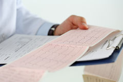 Male medicine doctor hands holding cardiogram chart. On clipboard pad closeup. Cardio therapeutist assistance, physician make cardiac physical, heart rate royalty free stock photography