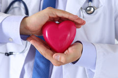 Male medicine doctor hands holding and covering red toy heart Stock Photos