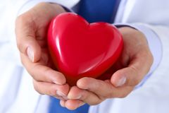 Male medicine doctor hands holding and covering red toy heart Royalty Free Stock Images