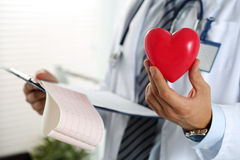 Male medicine doctor hands holding red toy heart. And cardiogram chart on clipboard closeup. Cardio therapeutist, physician make cardiac physical, heart rate stock photography