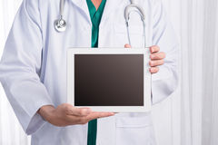 Male medicine doctor holding digital tablet pc and showing scree. N to camera Royalty Free Stock Photo