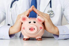 Male medicine doctor wearing blue tie holding and covering happy. Funny smiling piggybank in hands closeup. Medical service economy, health care savings and Stock Photo
