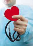 Male medicine doctor wearing hold in hands red toy heart and stethoscope closeup black background. Cardio therapeutist, physician Stock Photo