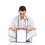 Male medicine student holding a clipboard. Young male doctor showing a clipboard sitting on a floor with legs crossed and reading. Full length studio shot Royalty Free Stock Images