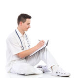 Male medicine student writing. Young male doctor sitting on a floor and writing on a clipboard. Full length studio shot isolated on white Royalty Free Stock Images