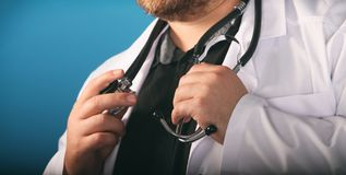 Male medicine therapeutist doctor hands holding stethoscope on his chest in the hand closeup. Physician is waiting for patient royalty free stock photos