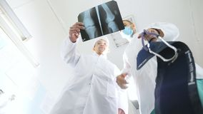Male medics consult with each other while looking at x ray image. Two caucasian doctors view mri picture and discussing. About it. Medical workers in hospital stock footage
