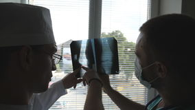 Male medics consult with each other while looking at x ray image. Two doctors view mri picture and discussing about it. Medical workers in hospital examine x stock footage