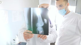 Male medics consult with each other while looking at x ray image. Medical workers in hospital examine x-ray prints. Two stock footage