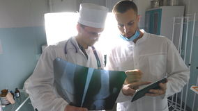 Male medics using tablet pc while consult with each other about x ray image of patient. Medical workers in hospital. Examine x-ray prints. Two caucasian doctors stock video footage