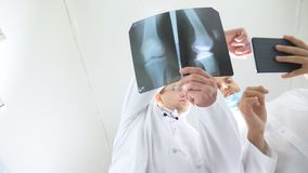 Male medics using tablet pc while consult with each other about x ray image of patient. Medical workers in hospital. Examine x-ray prints. Two caucasian doctors stock video