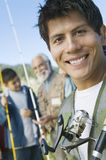 Male members of family on fishing trip. Male members of three generation family on fishing trip, focus on mid adult man, (portrait stock images