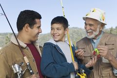 Male members of family on fishing trip. Male members of three generation family on fishing trip, smiling royalty free stock photo