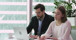 Male mentor helping female intern with corporate software in office
