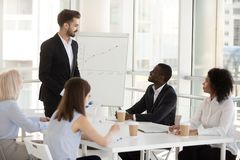 Male mentor give flipchart presentation interacting with workers. Smiling male employee give flipchart presentation at briefing with colleagues, positive mentor stock image