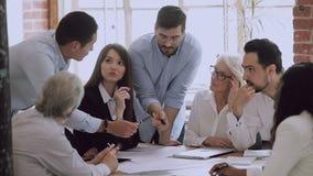 Male mentor training employees group explaining work plan at meeting