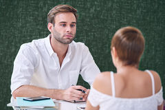Male mentor tutoring his female student in local coffee shop Royalty Free Stock Photos