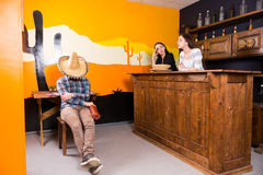 Male in a Mexican bar got drunk and fell asleep sitting on a cha. Ir and covered his face with a sombrero, female workers of bar look at him disapprovingly stock photo