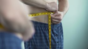 Male with middle-aged crisis measuring his body size, afraid of getting fat. Stock footage stock video footage