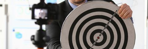 Male millennial vlogger hold target darst. In hands. Fast money business startup concept financial freedom aganist whiteboard background royalty free stock image