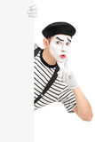 Male mime artist holding a blank panel and gesturing silence wit royalty free stock photo