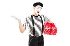 Male mime artist holding a gift box and gesturing with his hand. Isolated on white background Royalty Free Stock Photography