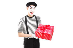 Male mime artist holding a gift box and looking at camera Royalty Free Stock Photo